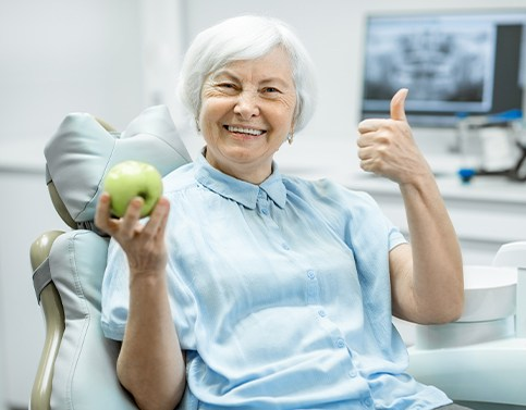 Senior woman holding an apple after all on 4 dental implant tooth replacement