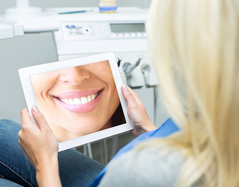 Woman looking at her virtual smile design on tablet computer