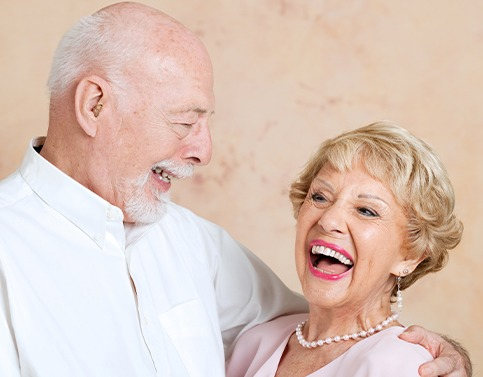 Older couple smiling after denture tooth replacement