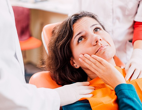 Woman in need of emergency dentistry holding cheek