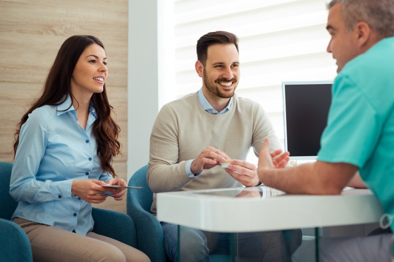 Couple smiling while talking to cosmetic dentist in office