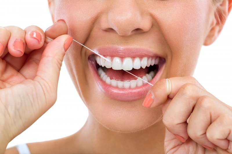 Closeup of woman smiling while brushing her teeth